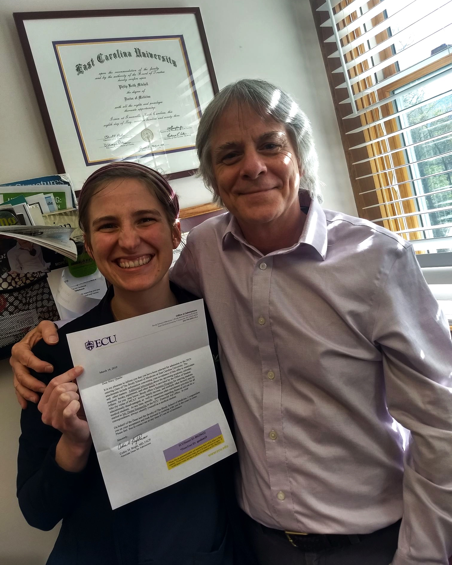2017 Fellow Mary Quaile poses with medical school acceptance letter and mentor Dr. Philip Mitchell of Celo Health Center in Burnsville, NC.
