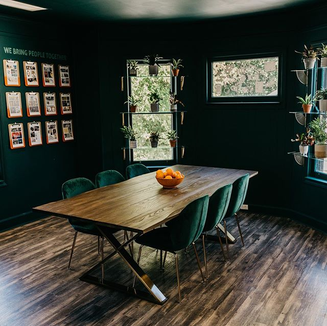 """It's unanimous! Our team's absolute favorite space in our new office is the """"green room."""" When @manmanstudios suggested we go all green with it, we were super nervous but also trusted in her vision. It's all in the details. Scroll through 👉🏼for before pictures! ✅ Fresh green paint on all walls & ceiling via partner @dools23 ✅ Custom glass shelves with living potted plants via teammate @mollamac ✅ Extra long gathering table from @wayfairprofessional with oranges in an orange bowl #orangeonorange ✅ Portfolio wall with orange-dipped clipboards featuring client work and arranged underneath our brand purpose """"We Bring People Together"""" (hung by our dad!) ✅ Green velvet chairs with golden legs to match the table ✅ White decals on the window to match our new iconography from @elliebrands  It's amazing what your environment can do to spark energy, camaraderie and creativity. Thanks to everyone who helped bring this to life!  #OfficeDesign #DooleySocialStudio #SocialMedia #InteriorDesign #inspo"""
