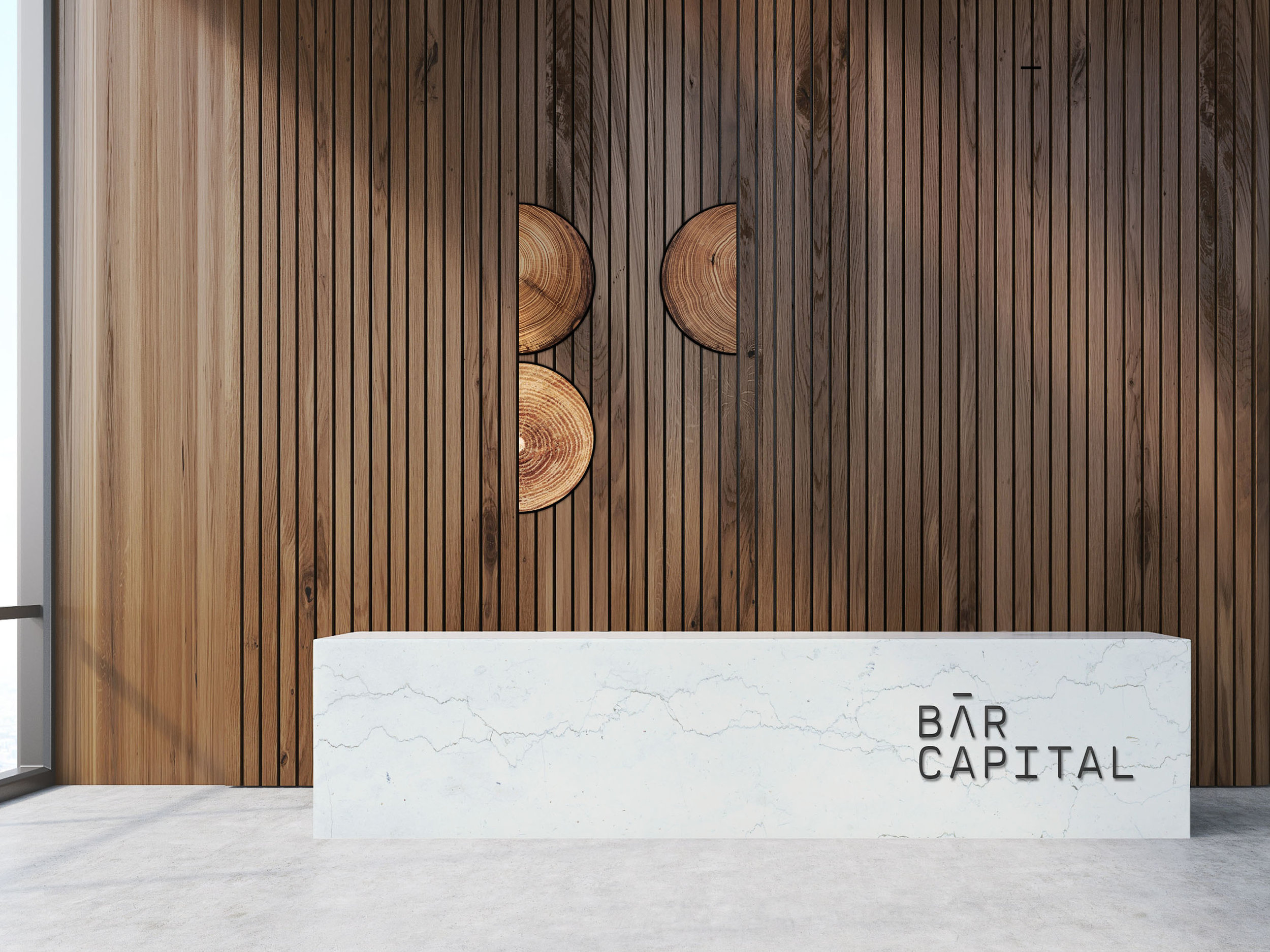 - —We developed concepts for Bar Capital's eventual lobby. The orderly wooden, shiplap wall is broken up by the logo constructed with cross section cuts from a tree stump. It continues the core tenet of celebrating natural materials as well as championing imperfections and the unpredictability of nature.