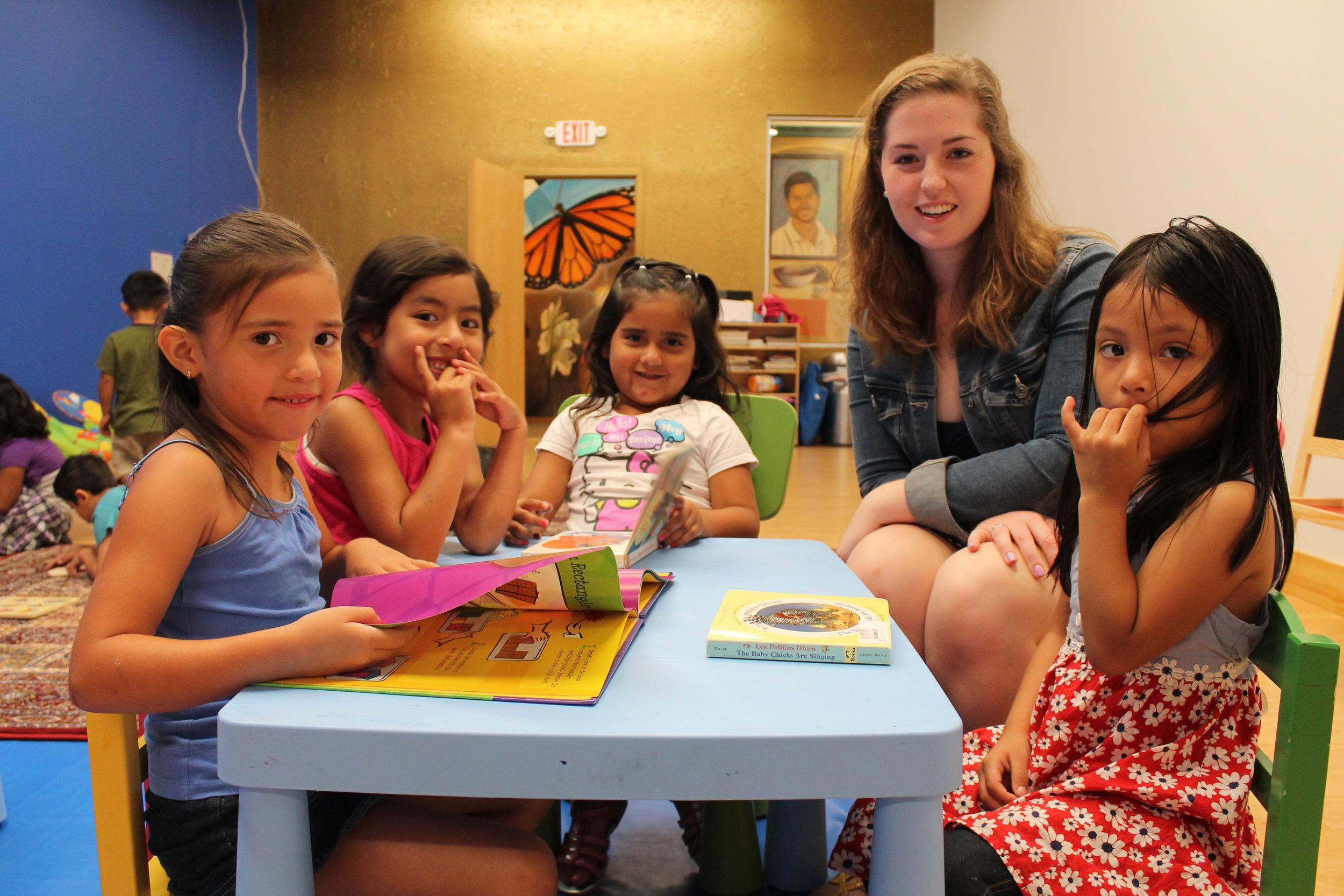 Descripción de foto: Niñes en la guardería Montessori leyendo libros.
