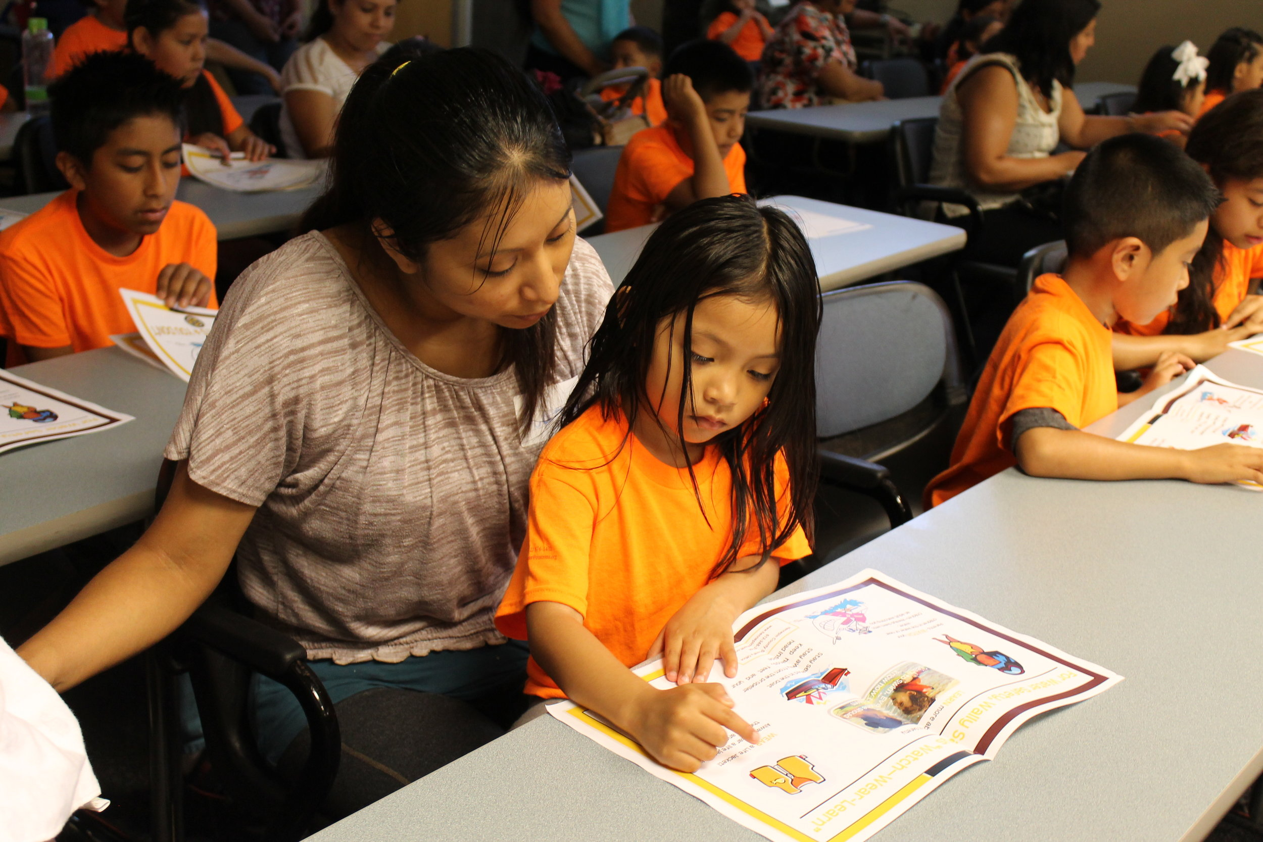 Photo caption: Be@School family. Mother and daughter reading a book.