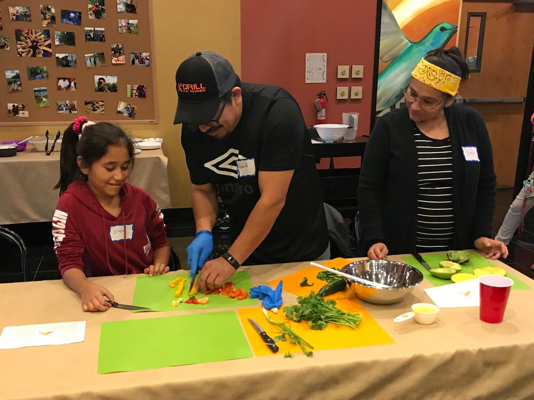 Descripción de foto: Participantes del programa Nutrición Familiar cocinando recetas saludables.
