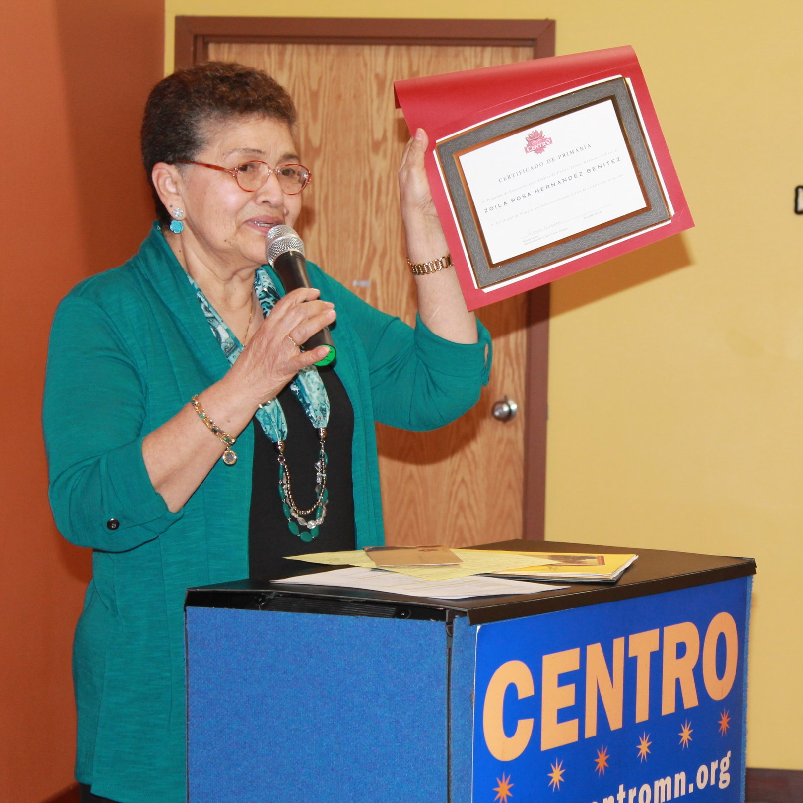 Photo caption: Adult Literacy participant receiving her graduation diploma.