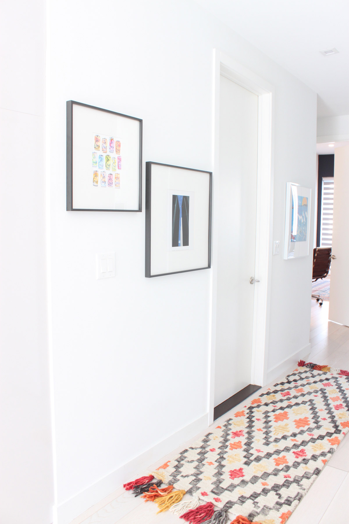 A mustard and pink colored morrocan rug runner in a white hallway with two framed photos on the wall.
