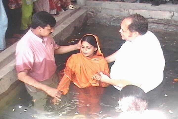 Apostle Barr baptizing a woman in Pakistan.