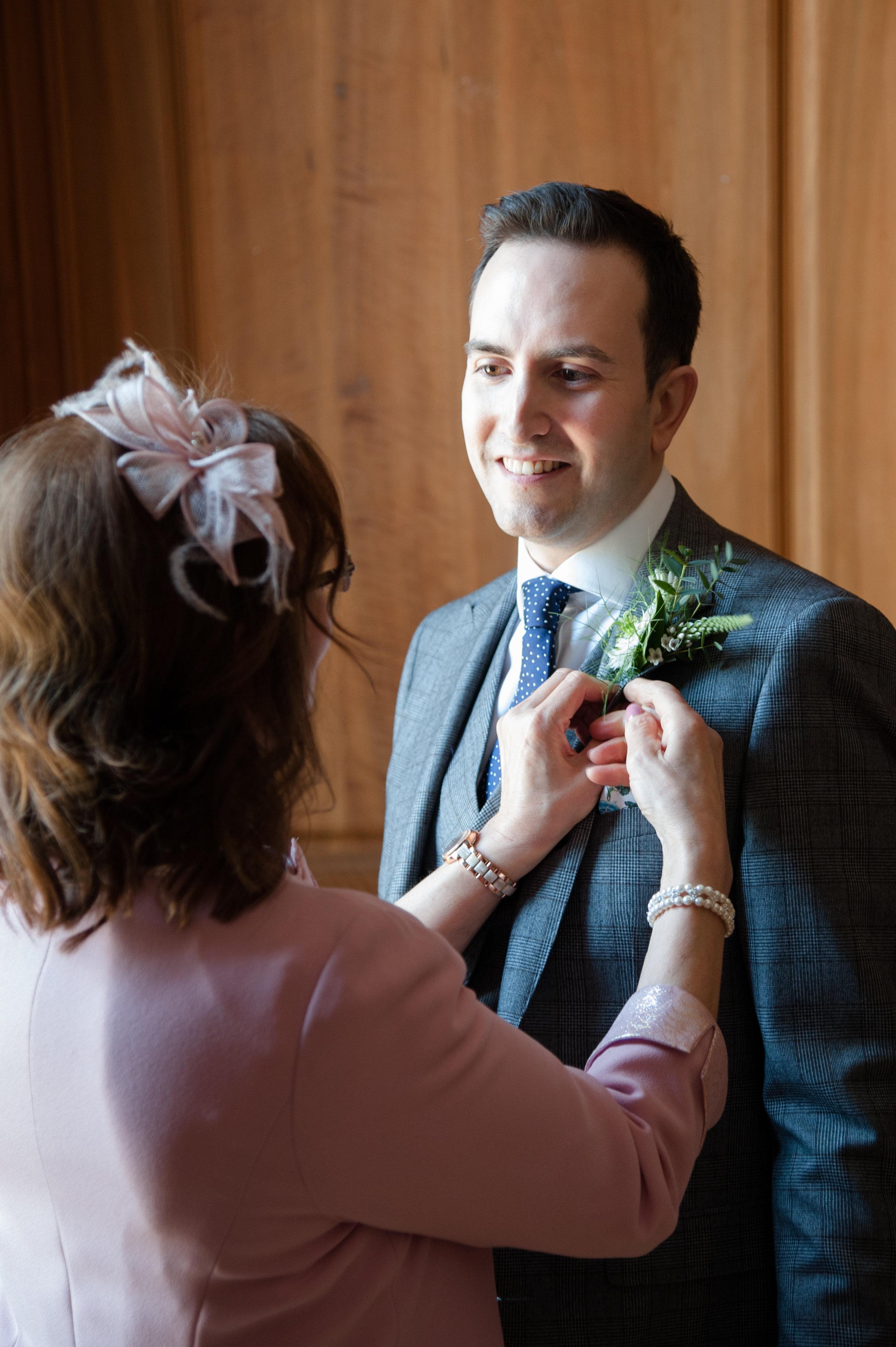 Mum attaching Filipe's buttonhole