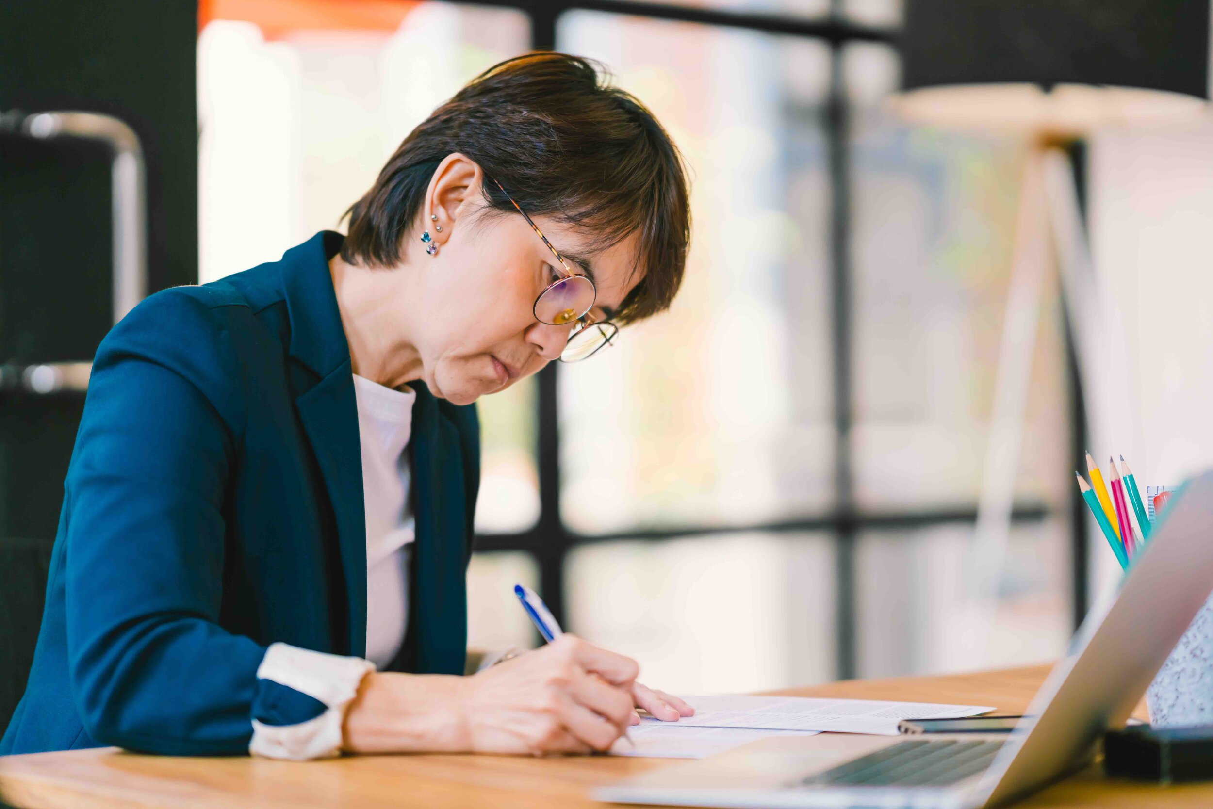 Canva - Beautiful middle age Asian woman working on paperwork in modern contemporary office, with laptop computer. Business owner, entrepreneur, executive manager, or employee office worker concept.jpg