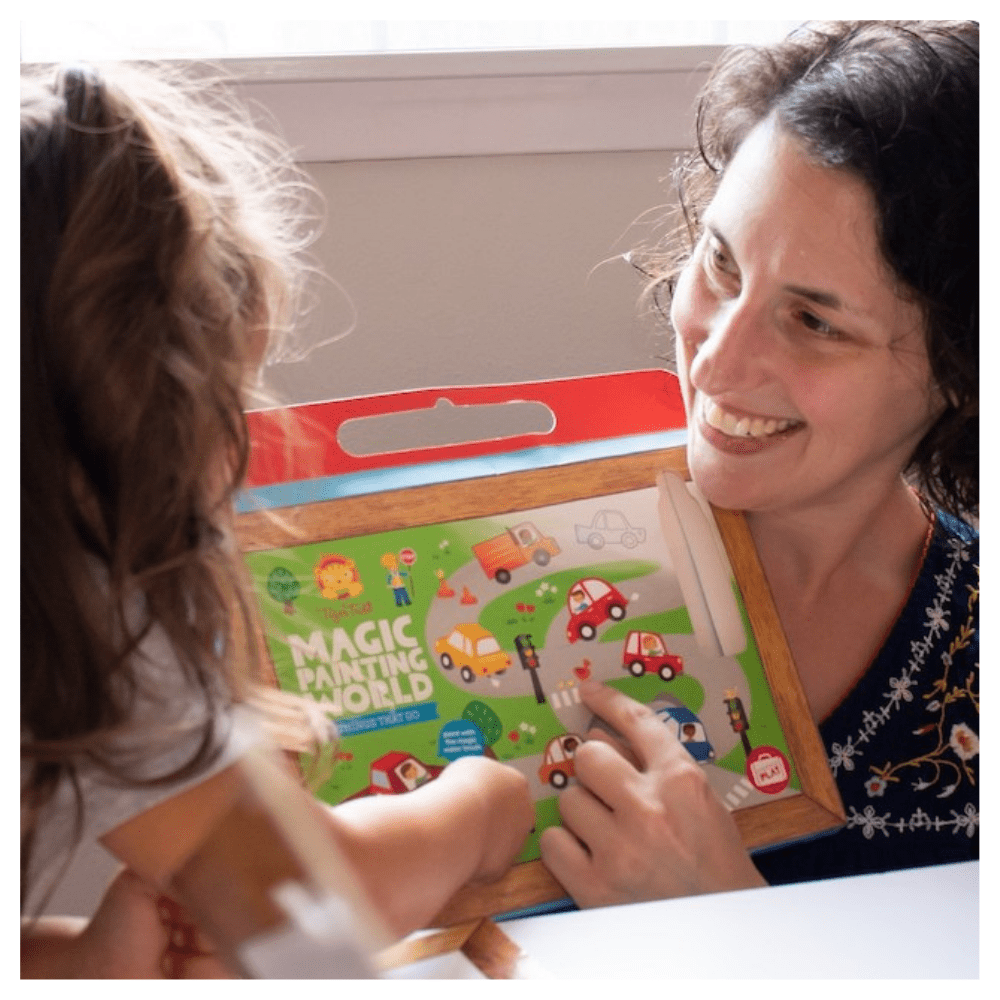 Rebecca points at magic painting book with child.png