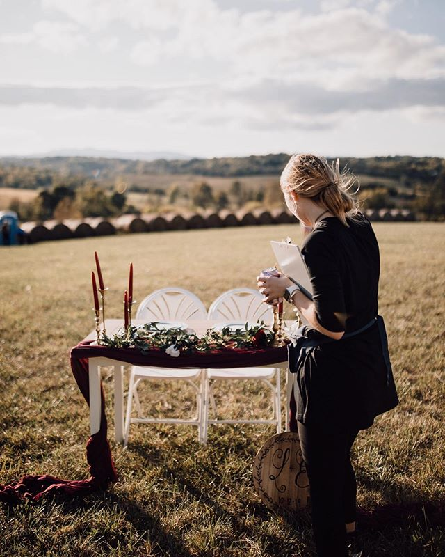 A little behind the scenes shot from my boho mountain wedding this past weekend. It was pretty windy up on that hill, and during the ceremony a strong gust of wind whipped all the decor off their cute little sweetheart table (which can we take a moment to obsess over those gorgeous, thrifted candlesticks?!) It's the little moments and details like this that, in my opinion, show the importance of having a wedding planner and day-of coordinator. Not only did I make sure that we stayed on time and that everyone knew what they were supposed to be doing - but I took care of the little details. So yes, it might just look like I'm adjusting a candle. But to me, it shows taking care of my clients down to the very last detail to make sure they don't have to worry about a thing. ✨ 📷@juliamichaelco