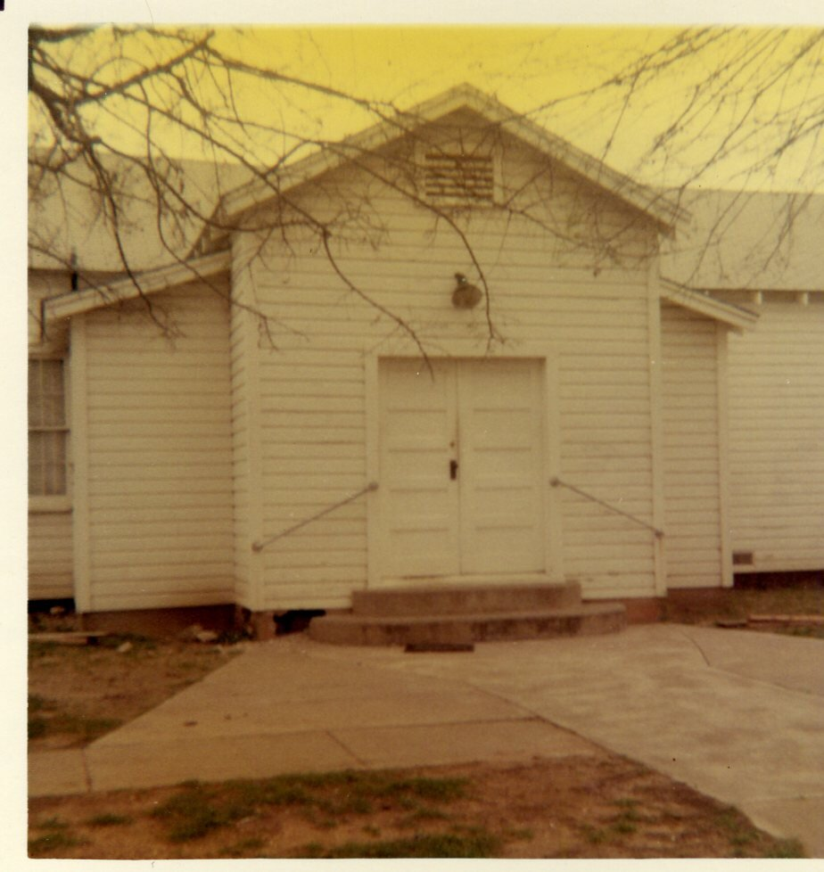 The 'towash building' - This photograph, taken before 1968, is one of the few photographs remaining of the building that was on the grounds prior to the one that stands today. This building would be dismantled and taken out of town on trailers to a field outside of town.