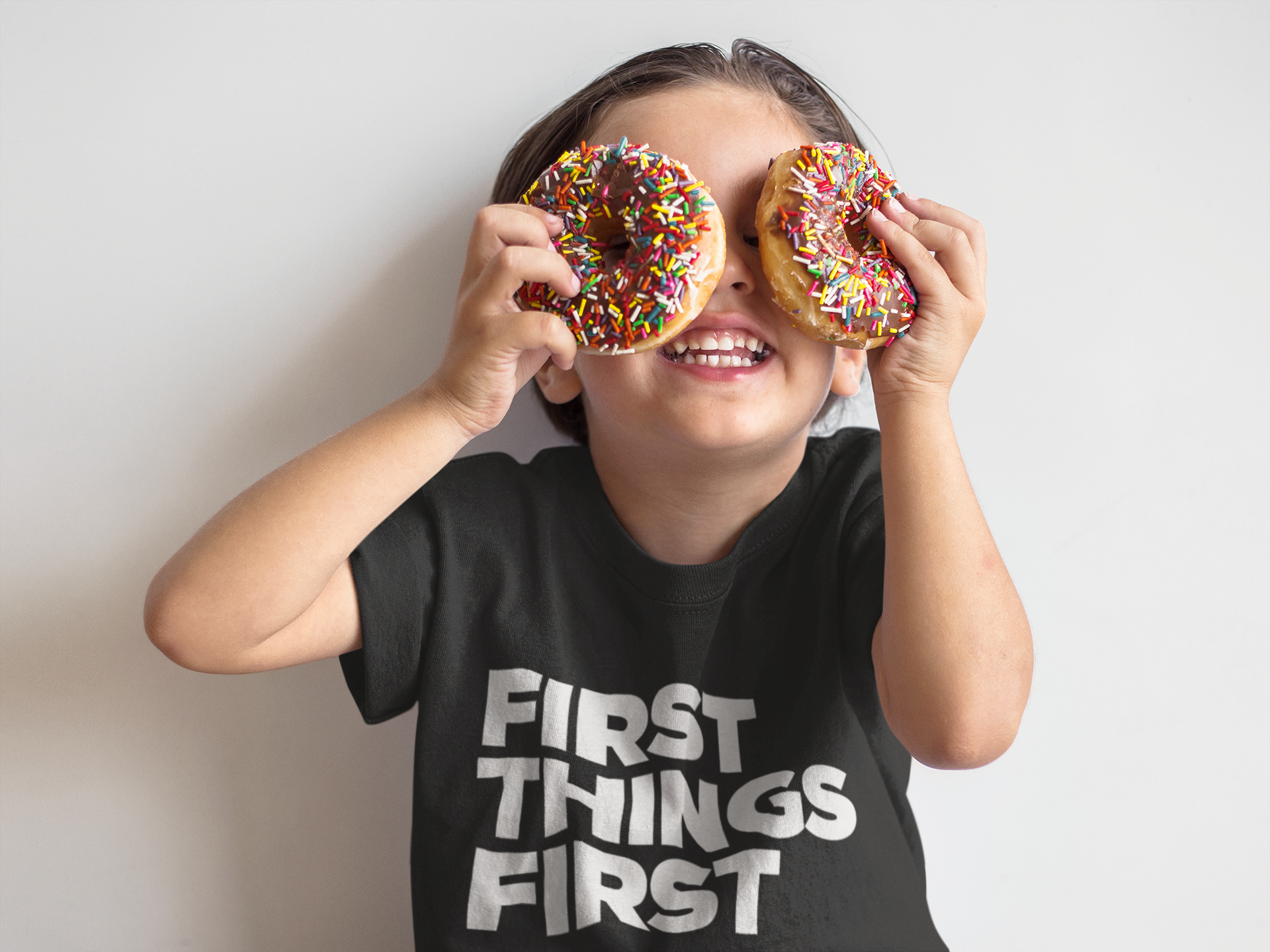 boy-playing-with-donuts-while-wearing-a-t-shirt-mockup-against-a-white-wall-a16139.png