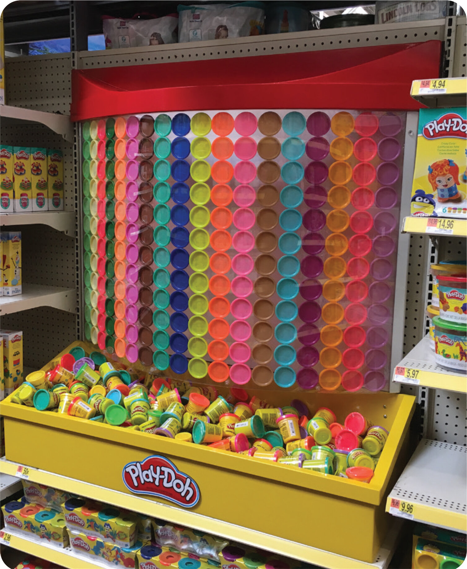 PlayDoh Shelf Merchandiser   a. The Ask – Quickly assist PlayDoh's marketing agency with the design and production of a display prototype after they received a version from a different supplier that did not meet the creative vision. The display was needed for a critical buyer meeting.  b. The Approach – Using the original buyer-approved rendering, create a permanent dump-bin shelf unit featuring lids from the PlayDoh canisters to draw attention to the display in-aisle.  c. The Results – Designed, engineered and produced a limited production quantity for a regional test based on buyer approval from the display review. The buyer was so impressed with the quality of the display and how closely it matched the approved rendering that she shared it across her merchant organization.