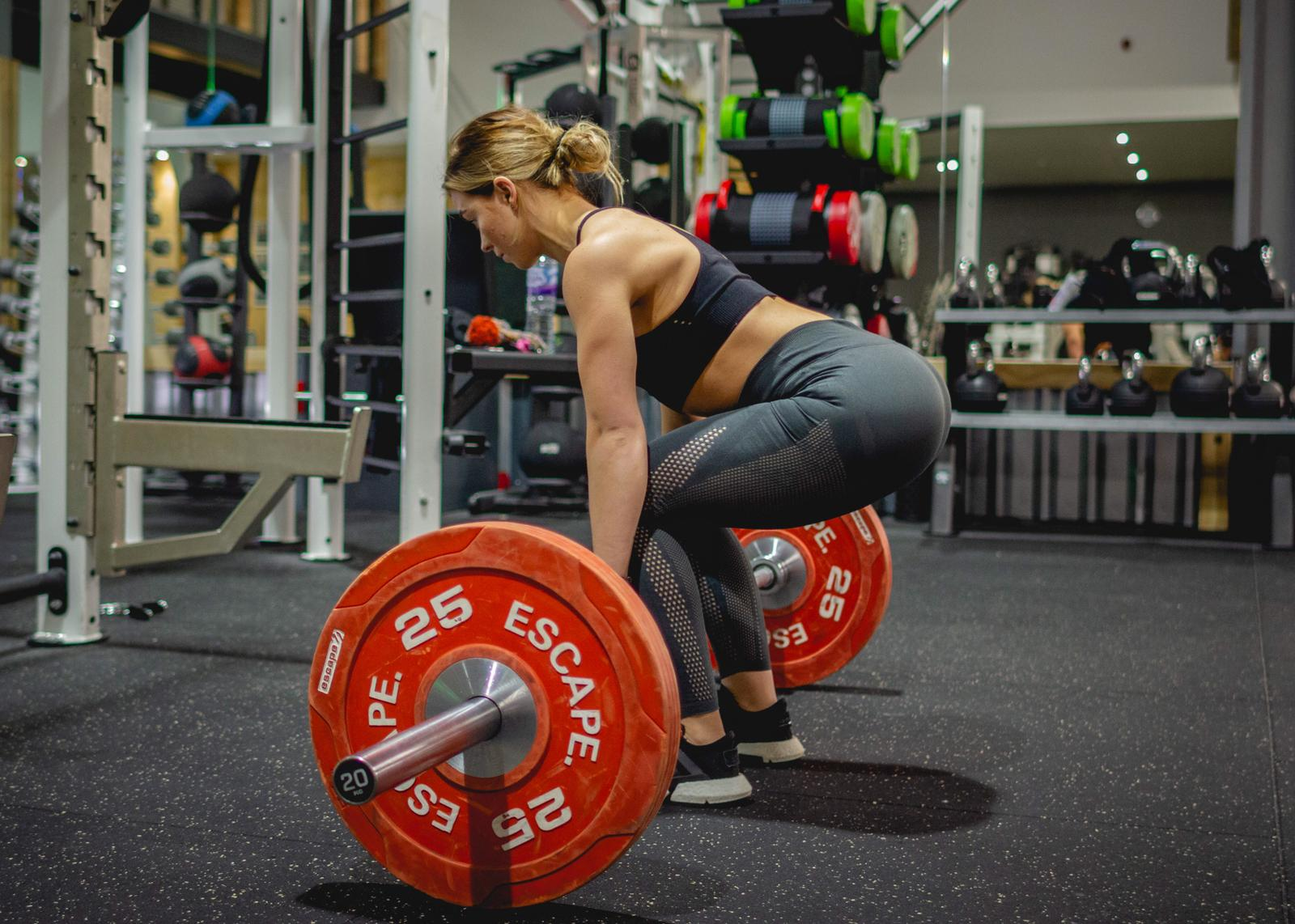 Female trainer performing deadlift