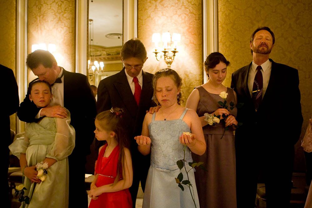 "Fathers and daughters pray together in the ballroom of the Broadmoor Hotel on May 16, 2008 in Colorado Springs, CO. The annual Father-Daughter Purity Ball, founded in 1998 by Randy and Lisa Wilson, focuses on the idea that a trustworthy and nurturing father will influence his daughter to lead a lifestyle of ""integrity and purity."""