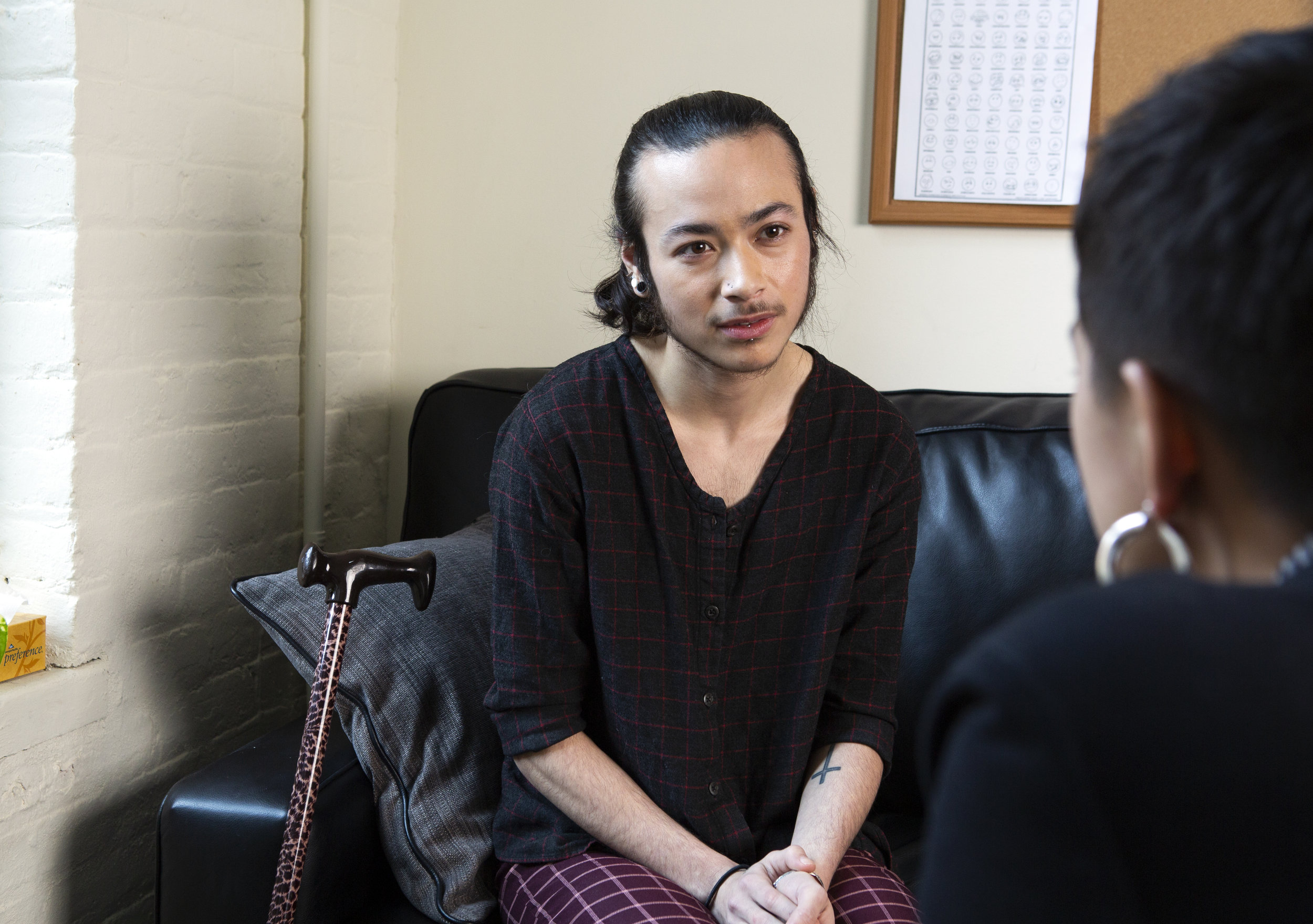 A genderqueer person sitting on a therapist's couch, listening