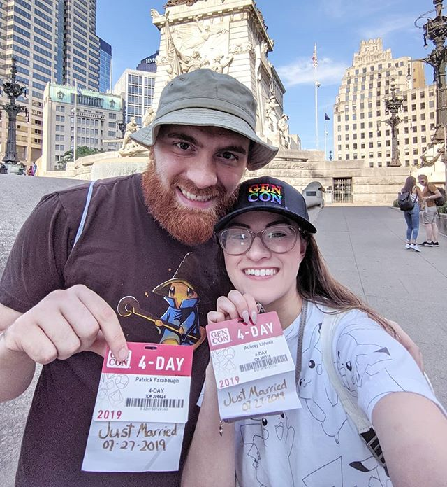 """Our Honeymoon 💕 & The Best Four Days in Gaming . . . . [Image description: Aubrey and her husband, Pat, are standing in front of a tall monument in Indy. They are smiling and holding their GenCon badges up. Their badges have ribbons on them that say """"just married."""" Pat is wearing his bucket hat and Aubrey is wearing a black baseball cap that says """"GenCon"""" in rainbow stitching.] . . . .  #honeymooners #honeymoon #gencon #gencon2019 #indy #indianapolis @gen_con  #gamergirl #gamers #boardgames #thebestfourdaysingaming #married #justmarried  #newhusband #newwife #wifey #waifu  #charmander #teeturtle #pikachu #pride #loveislove #gamerwife #filthymouthedwife"""