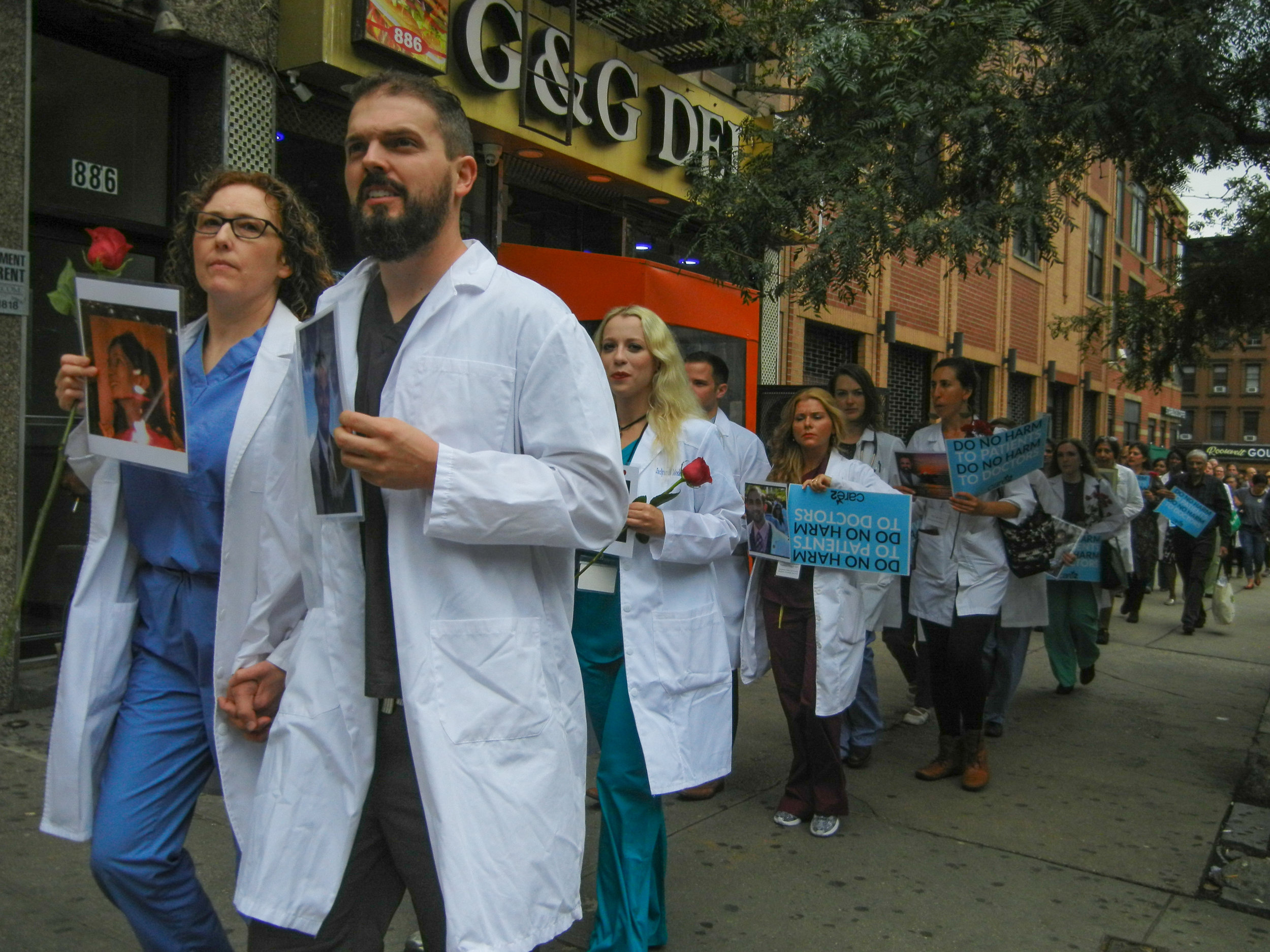 A procession of doctors, nurses, and medical professionals walk through Hell's Kitchen hand-in-hand in honor of their lost colleagues | Carolyn Adams