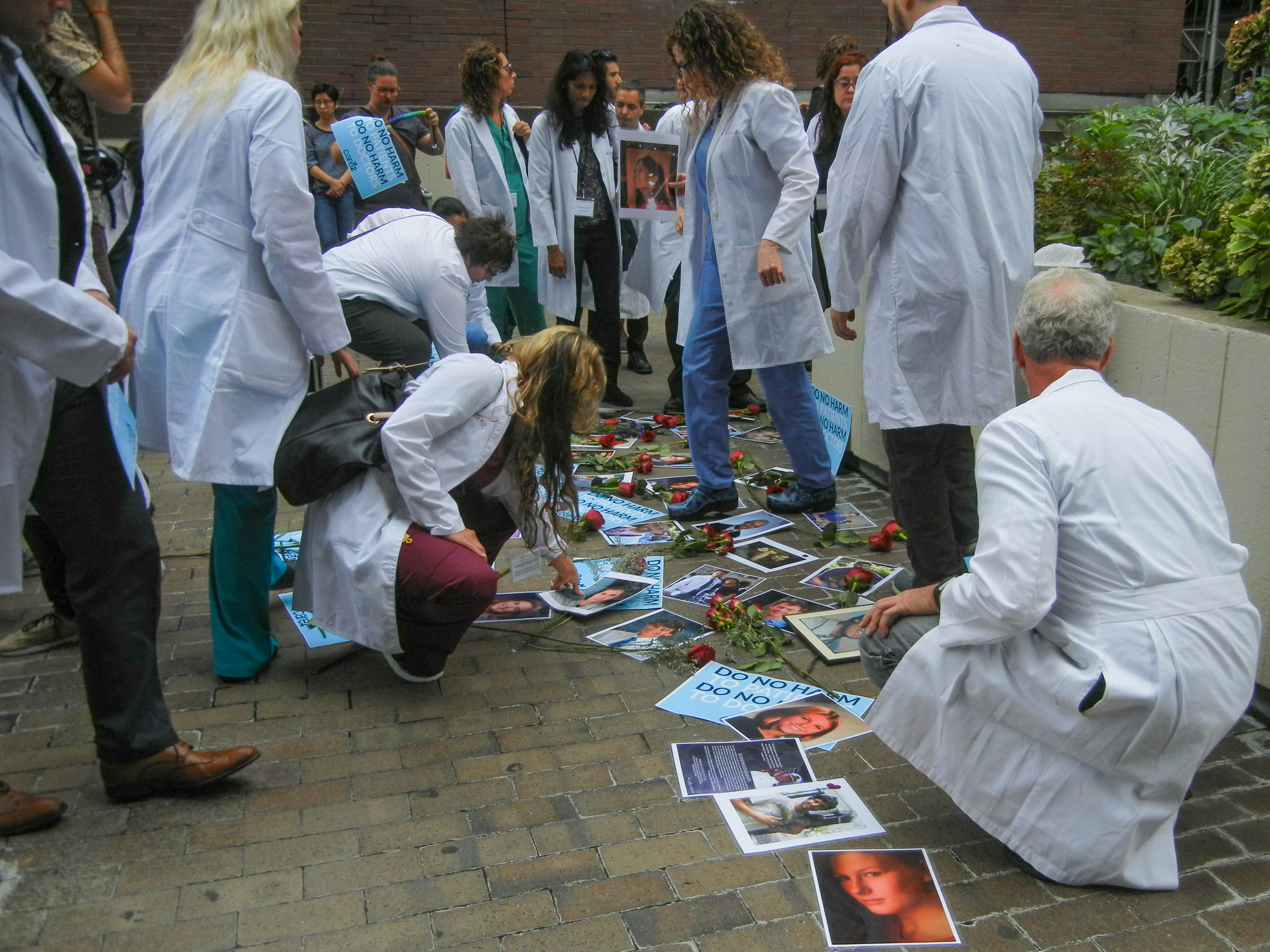 Doctors, medical professionals, family and friends laid down photos of those lost to suicide during a memorial at the site where Dr. Deelshad Joomun died | Carolyn Adams