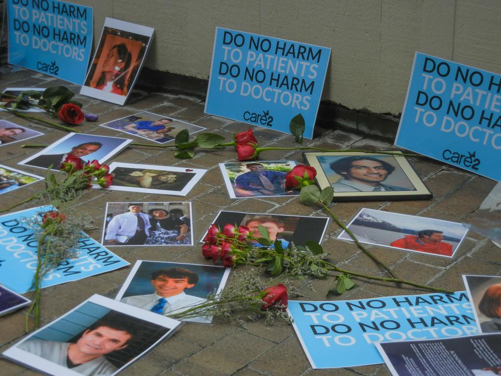 Close-up of photos and signs during memorial | Carolyn Adams