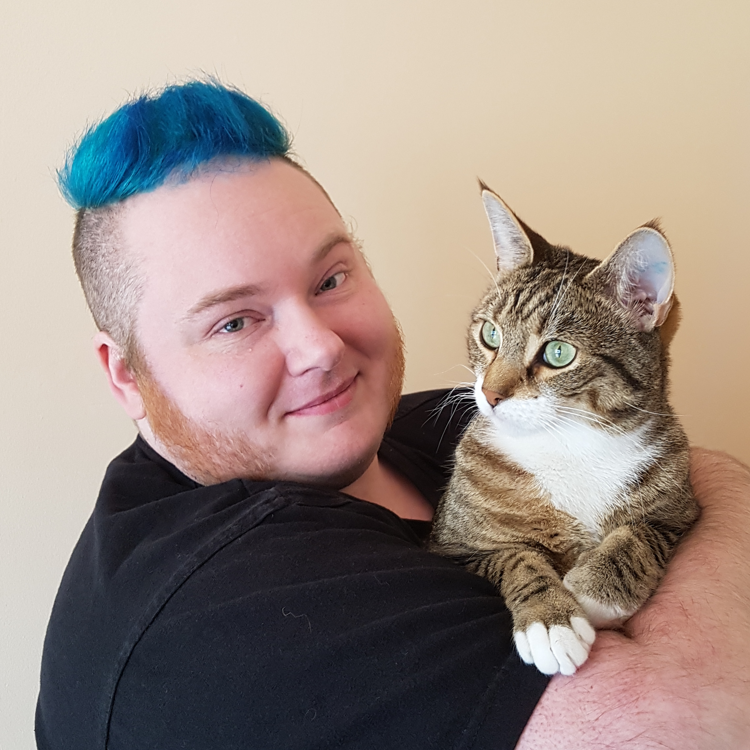 A photo of Erin Kyan, a white man with blue hair and ginger sideburns, holding a tabby cat.