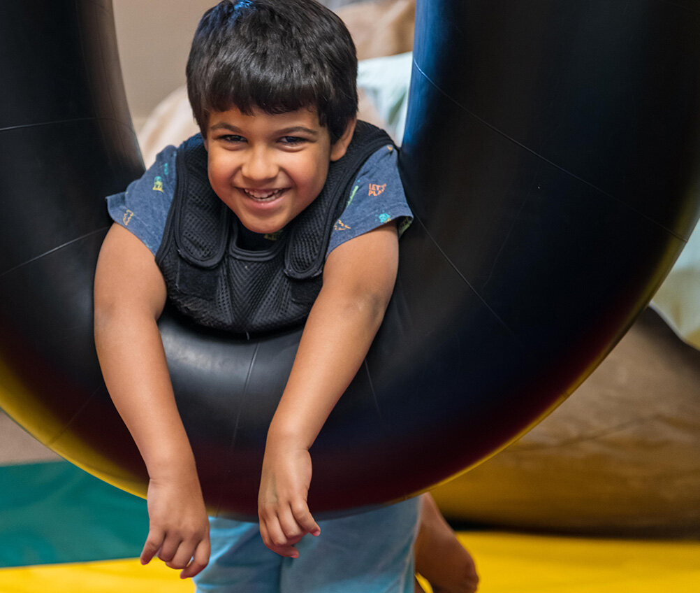 Smiling happy boy on tire swing during therapy at Sensory Processing 4 Kids office