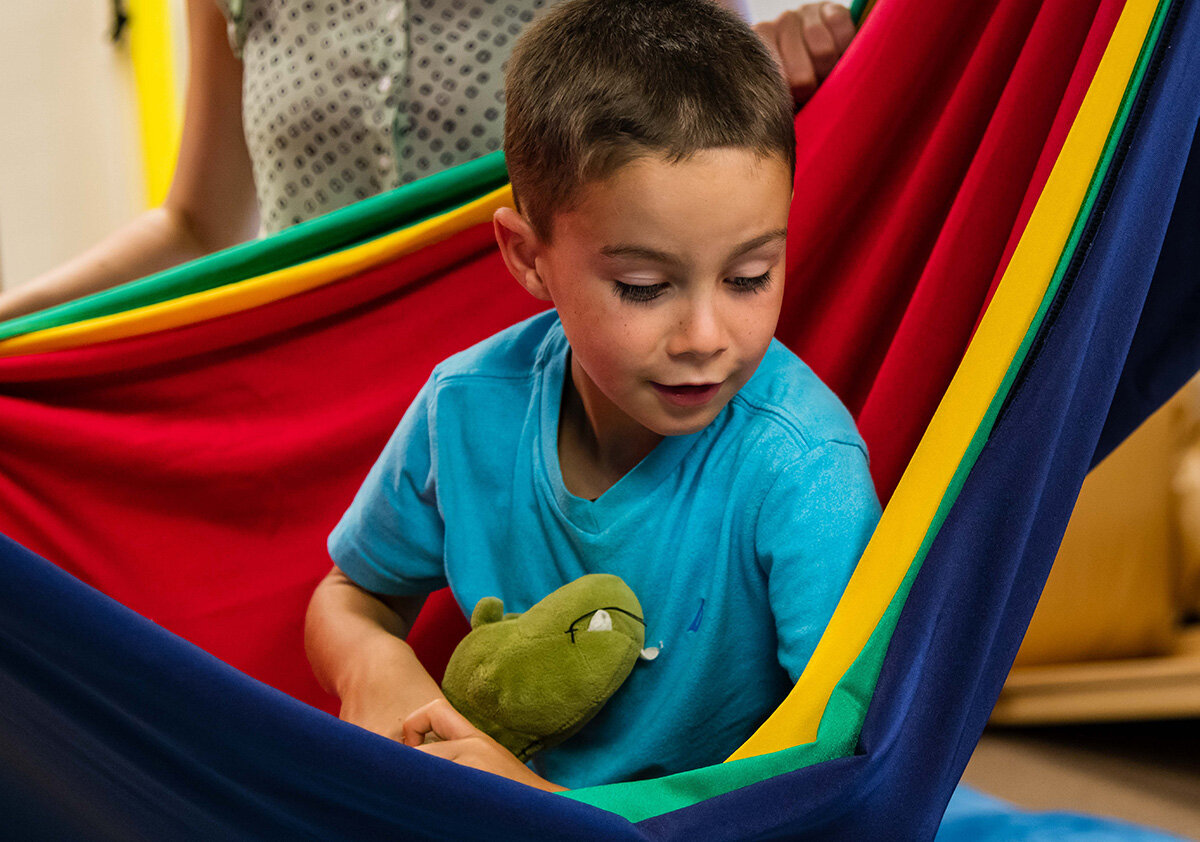 Boy on hammock during therapy session at Sensory Processing 4 Kids office