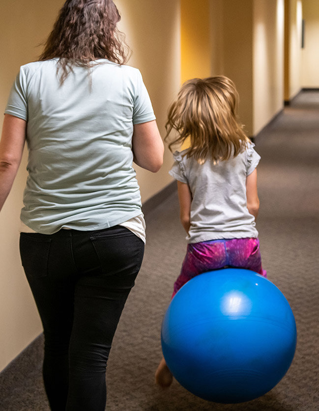 Girl on exercise ball during therapy session