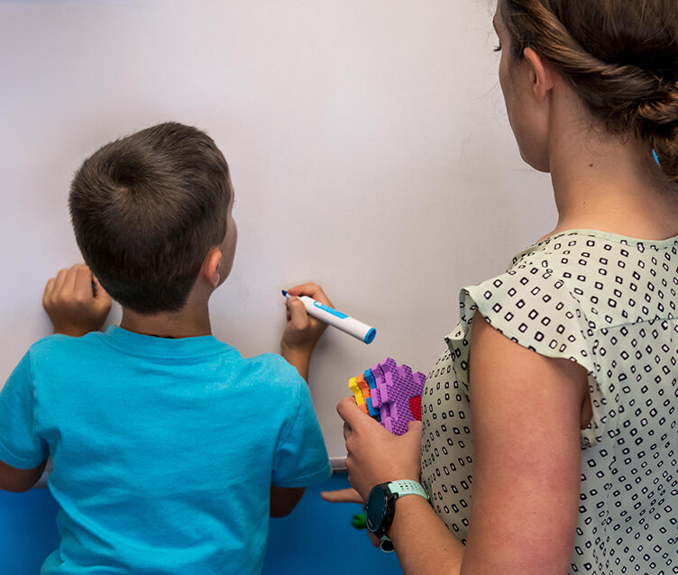 Boy writing with occupational therapist