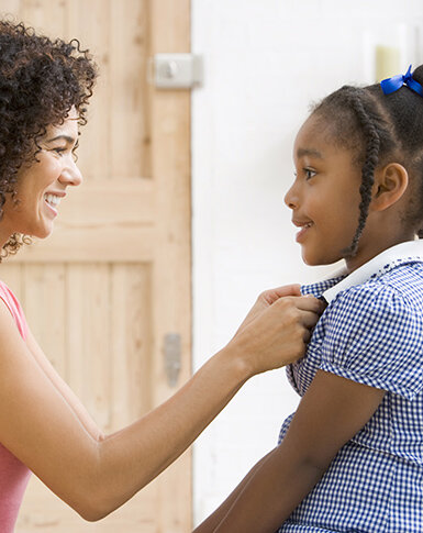 Girl getting dressed for school during morning routine