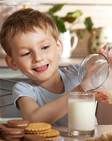 Boy independently pouring milk during peaceful meal