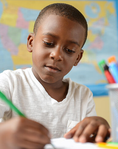 Boy writing in class and showing school improvement and success