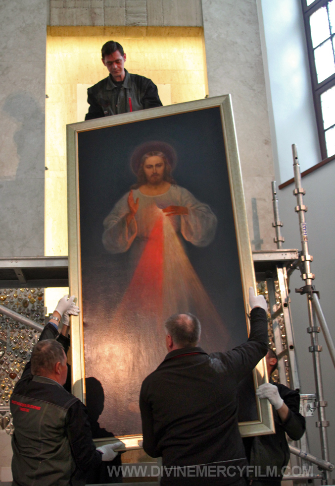 Workers carefully removed the priceless painting from the niche and gently brought it down to the floor.