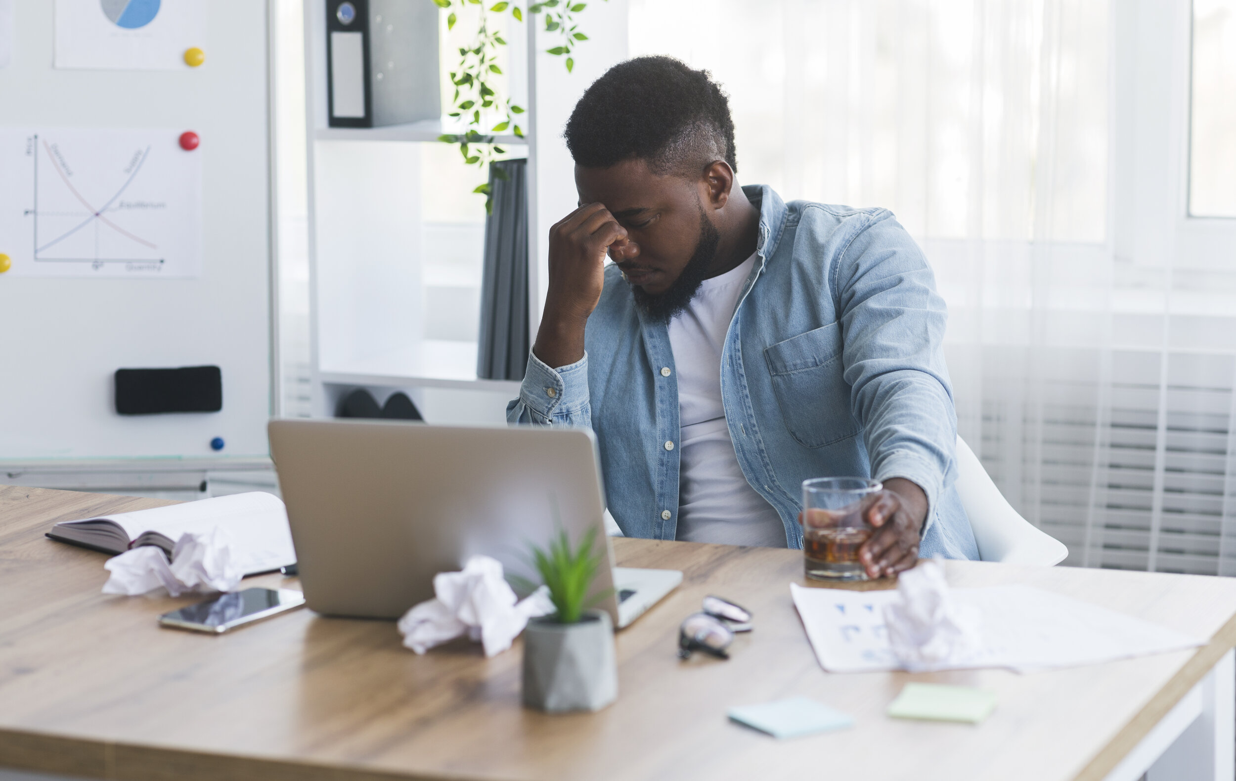 Stressed african american employee drinking alcohol at workplace