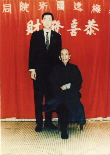 Grandmaster Moy Yat standing beside his teacher, Grandmaster Yip Man.