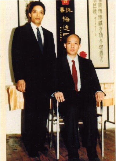 Grandmaster Moy Tung standing beside his teacher, Grandmaster Moy Yat.