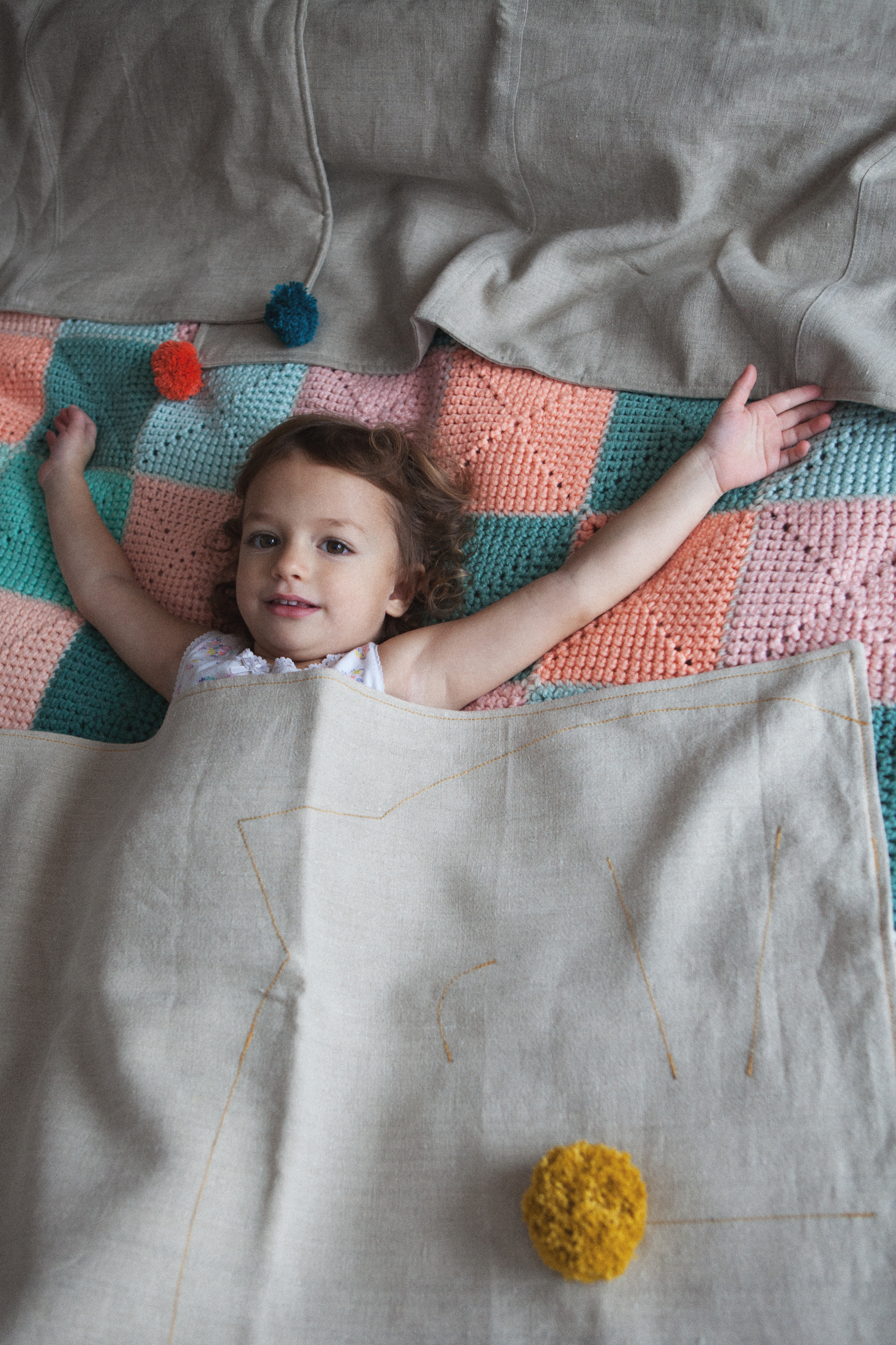 Organic natural toddler blanket made of pure hemp decorated with a yellow embroidered cat pattern.