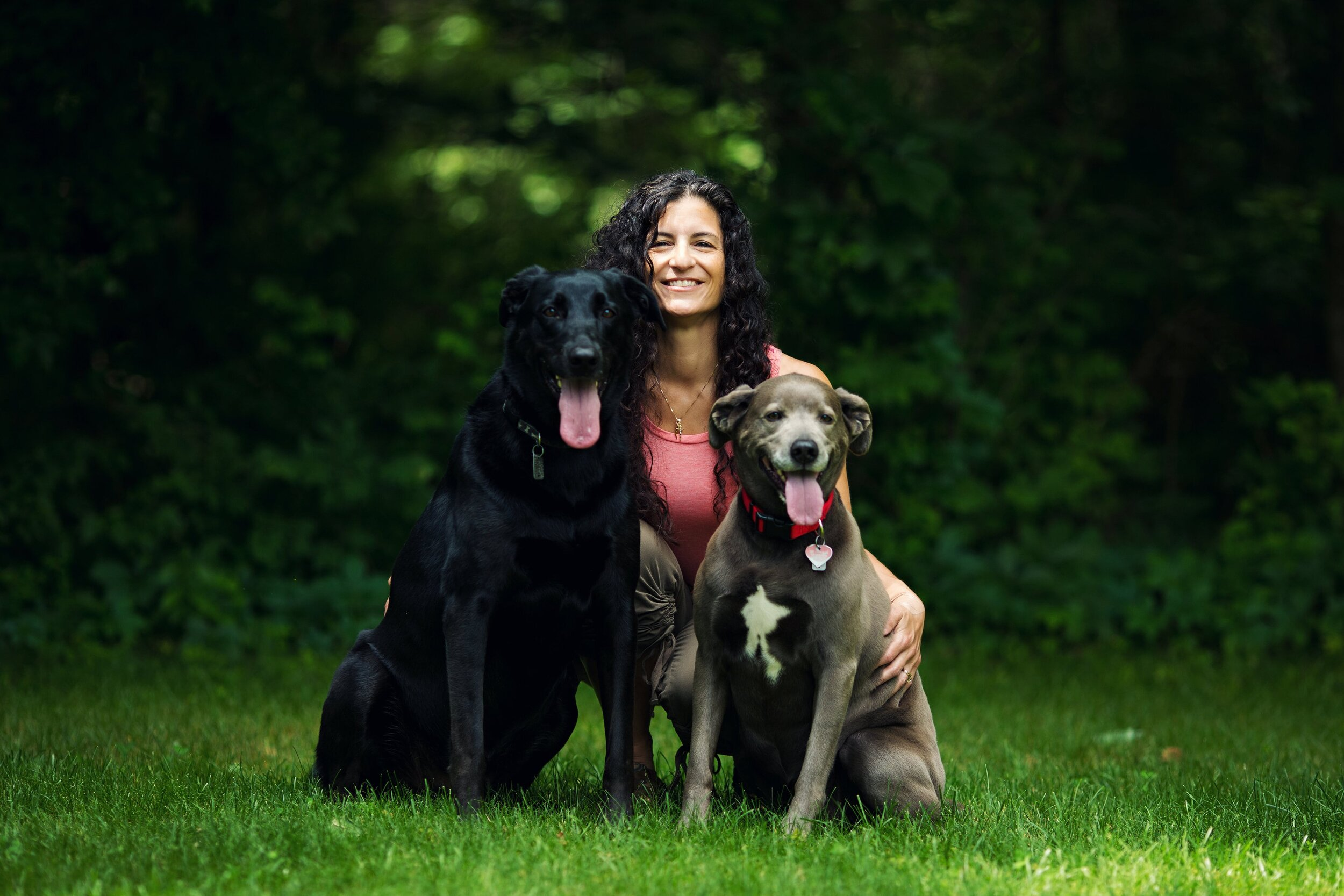 Janine kneeling in a field with her two dogs, Zoey and Dakota