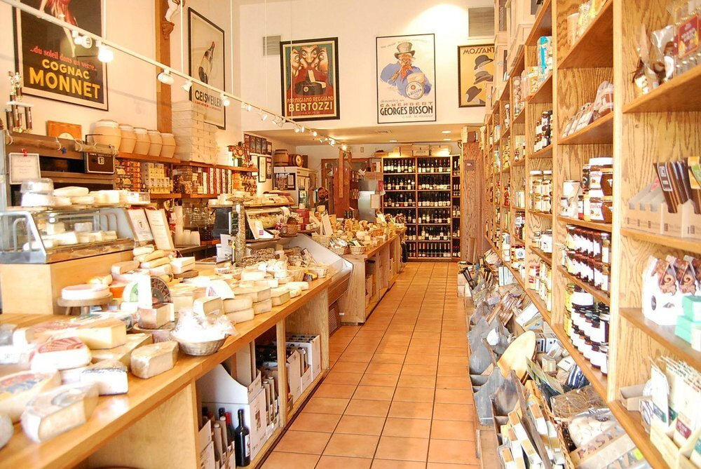 Photo of the front entrance of the Cheese Store of Beverly Hills, showing a large quantity of different cheeses and other various items
