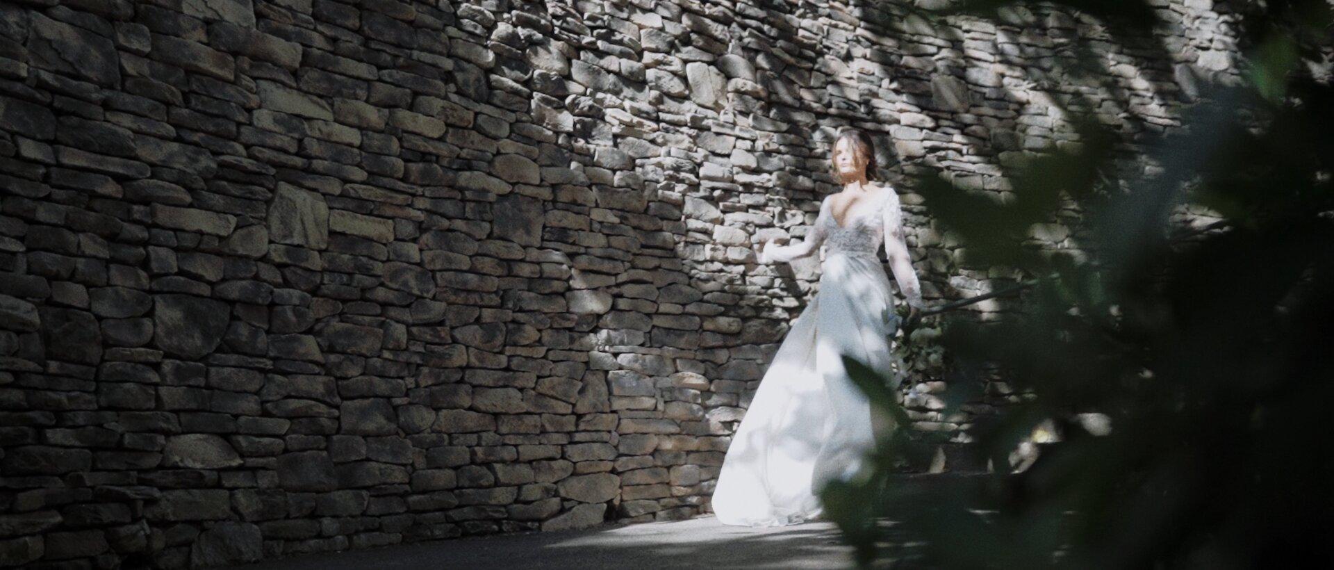 bride walking by Montage Kapalua stone wall