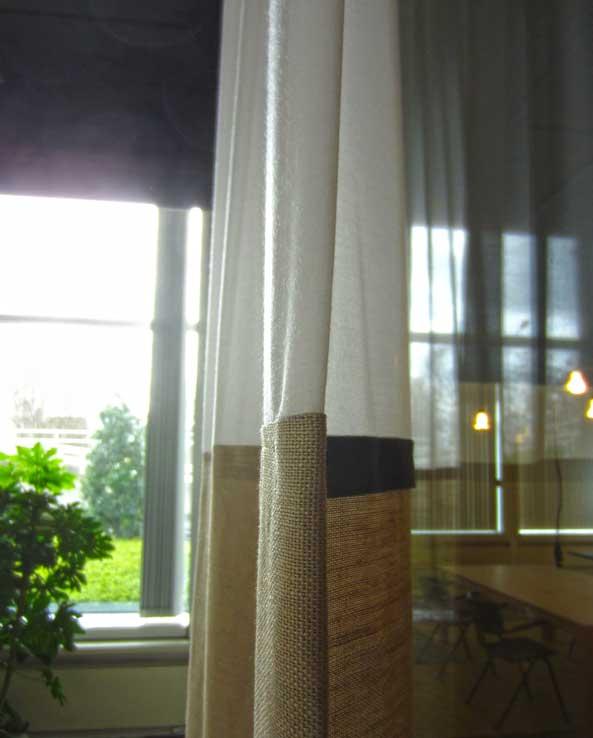 Kimik Design GordijnNo.33Subtiel Zicht - Een zacht zichtfilter van batist & ruw linen creëerden we voor deze vergaderruimte.Het gordijn sluit de vergaderruimte af en geeft de beoogde privacy maar geeft tegelijkertijd toch een gevoel van ruimte doordat er een subtiele doorkijk is naar de aangrenzende zaal. Door het gebruikt van dunne, lichte batist, met een iets zwaardere linnen, ontstaat er een mooi contrast van zacht & ruw, wat een mooie spanning geeft. De details moeten natuurlijk aan beide zijden mooi zijn, aangezien beide ruimtes zicht op het gordijn hebben wanneer deze gesloten is. De binnenzijde is rustig met de wit & ecru verdeling, de buitenzijde heeft contrasterende keperbanden welke een mooi accent in de vlakverdeling geven, reagerend op de omgevende ruimteKimik ontwerpt een maakt originele gordijnen voor jouw ruimte.De ontwerpen worden gemaakt in overleg, met een originele twist die jouw gordijnen uniek maken. Neem contact met ons op voor een eigen ontwerp of voor meer informatie!