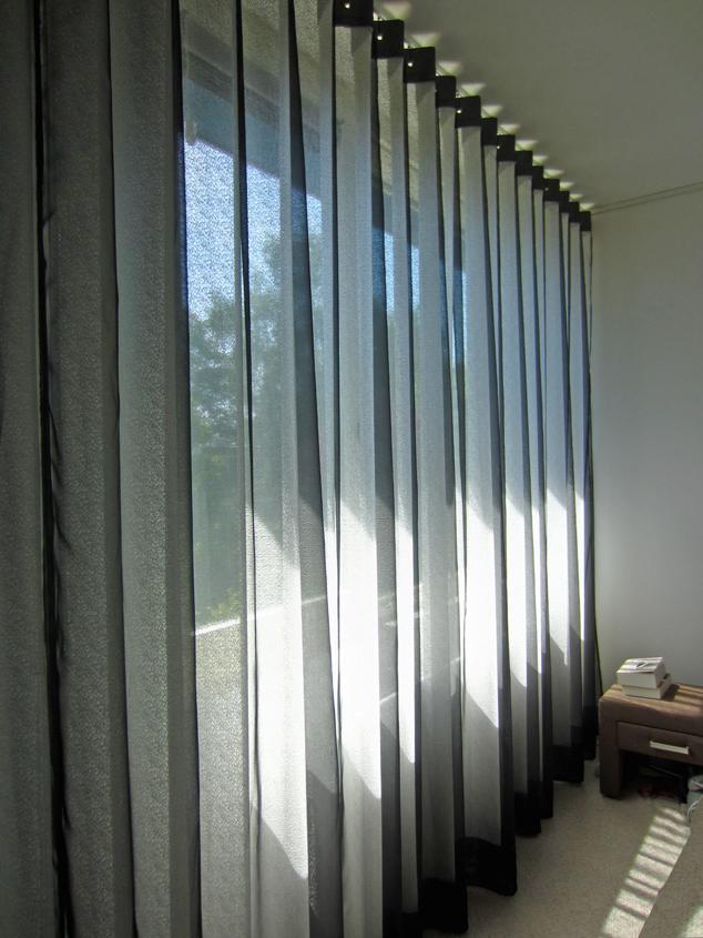 Kimik Design GordijnNo.31SpannendeSchaduwen - Deze slaapkamer heeft shutters aan de buitenzijde voor verduistering, maar voor wat extra sfeer werd binnen een Kimik-gordijn ontworpenDeze lagen textiel creëren een mooie intieme sfeer. De craquelé structuur van de witte stof is gecombineerd met een ultra dunne glanzende zwarte voile, wat een subtiel & spannend schaduw effect geeft wanneer het licht er doorheen valtKimik ontwerpt een maakt originele gordijnen voor jouw ruimte.De ontwerpen worden gemaakt in overleg, met een originele twist die jouw gordijnen uniek maken. Neem contact met ons op voor een eigen ontwerp of voor meer informatie!