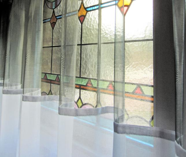 Kimik Design GordijnNo.25 Licht & Wit - Een simpele ingreep met een maximaal effectDe witte semi-transparante batist heeft een inzet van zilverachtige lasergewebezo transparant dat het prachtige glas in lood zichtbaar blijftNaast de voluptueuze jacquard gordijnen geven deze relatief eenvoudige materialen een mooi accent en houden de ruimte licht terwijl de inkijk tegengehouden wordtKimik ontwerpt een maakt originele gordijnen voor jouw ruimte.De ontwerpen worden gemaakt in overleg, met een originele twist die jouw gordijnen uniek maken. Neem contact met ons op voor een eigen ontwerp of voor meer informatie!