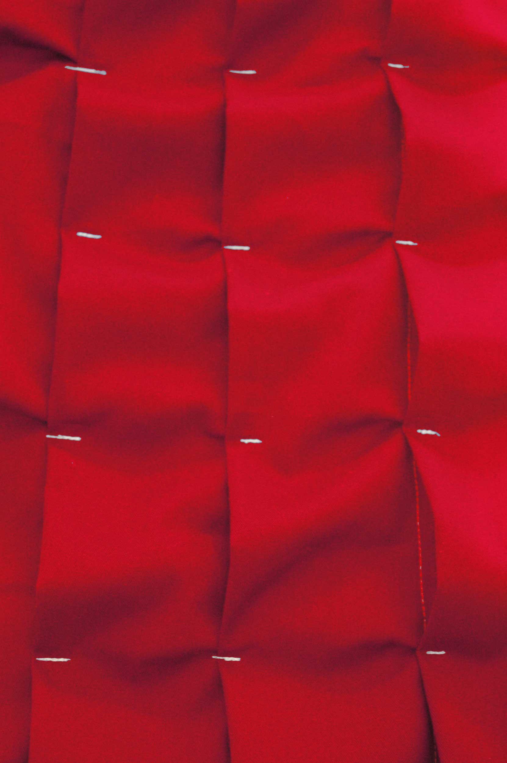 GordijnNo.2TheaterDoek - Het ontwerp van een origineel rood theatergordijn, maar dan wel met een twist.Het concept van het theatergordijn is enorm beïnvloed door de stof. Deze was een gift van de firma Ten Cate aan de stad Enschede. Het gekozen materiaal uit hun collectie wordt normaliter gebruikt voor tenten, werkkleding en uniformen. Doordat deze stof zelf niet aan de technische eisen van een theatertextiel voldoet (qua gewicht, licht en geluidsabsorptie) hebben we de stof 3 maal toe gevouwen over zijn eigen oppervlakte waardoor er een zwaar gordijn ontstaat met een driedimensionale structuur van geopende vierkanten.De compositie van vierkanten is een tegenbeweging tegen de rondlopende patronen in de foyer en het auditorium. Terwijl de halve cirkel, van waaruit de gevouwen structuur plooien openvallen, indirect refereert aan diezelfde cirkels.Een zwart wit kamperkoelie print is subtiel verborgen in de vouwen en plooien van het gordijn, ze komt alleen tevoorschijn wanneer het gordijn beweegt.Kimik ontwerpt een maakt originele gordijnen voor jouw ruimte.De ontwerpen worden gemaakt in overleg, met een originele twist die jouw gordijnen uniek maken. Neem contact met ons op voor een eigen ontwerp of voor meer informatie!
