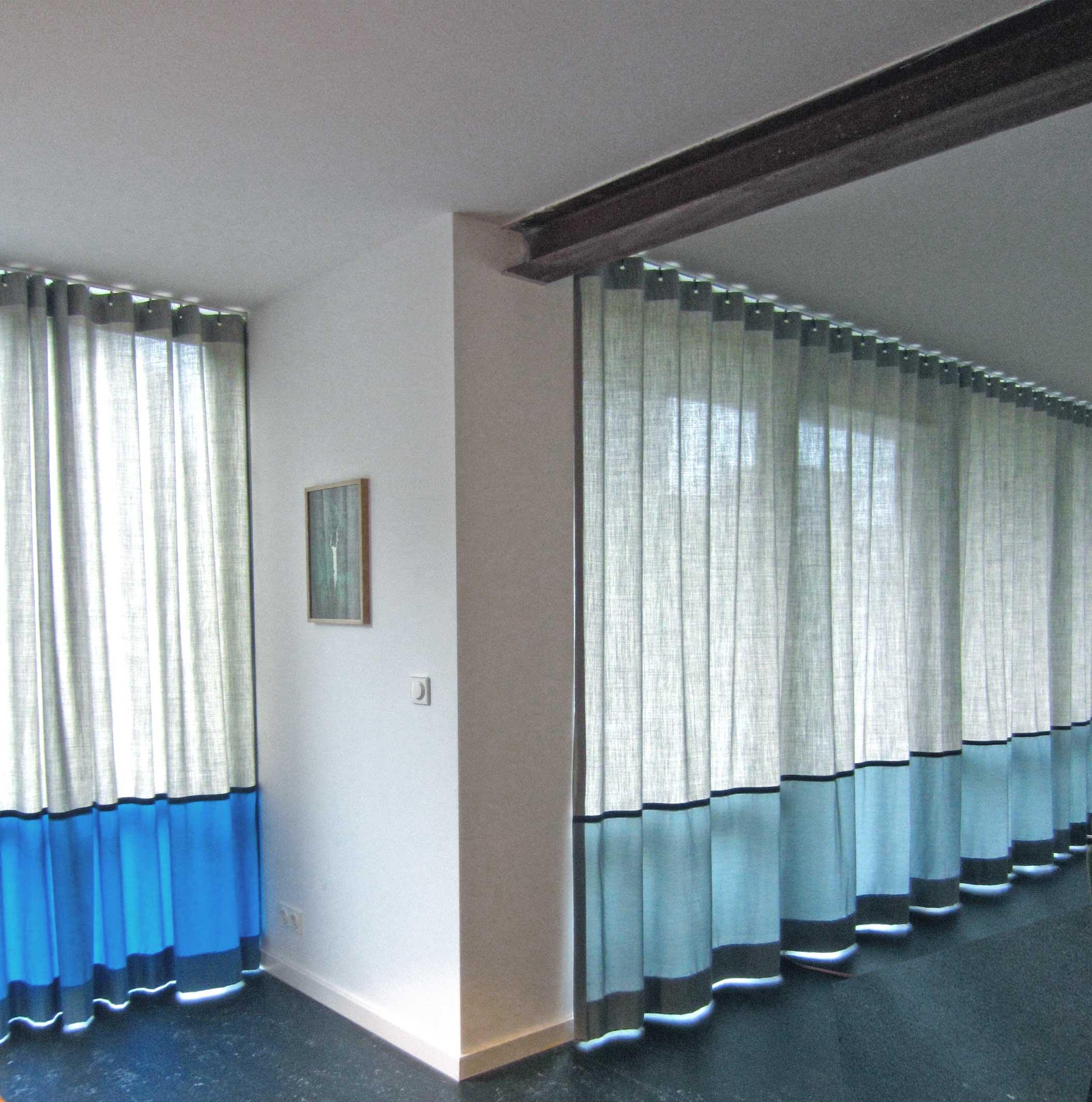 Kimik Design GordijnNo.37Bauhaus - Een markant gordijn opgebouwd uit een laag zachte open geweven grijs gemêleerde wol, gecombineerd met een felle dicht geweven contrasterende stof, geaccentueerd door een zwarte keper bandDe horizontale vlakverdeling volgt de architectuur en houd de lijnwerk van de ramen aan, doorlopend in de aangrenzende kamer, maar daar verspringend van grijs naar een felle diepblauwHet geheel is geïnspireerd op het Bauhaus, wat ook een inspiratie vormde voor de gehele inrichting van dit prachtige 'klushuis'Kimik ontwerpt een maakt originele gordijnen voor jouw ruimte.De ontwerpen worden gemaakt in overleg, met een originele twist die jouw gordijnen uniek maken. Neem contact met ons op voor een eigen ontwerp of voor meer informatie!