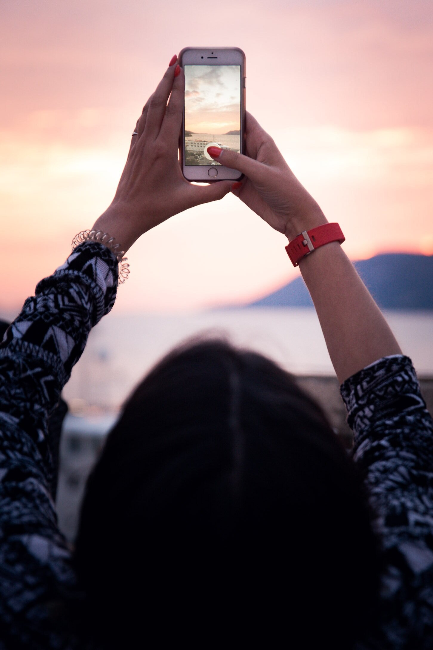 A young woman holds her mobile phone up to snap a photo of a sunset on the Mediterranean sea.