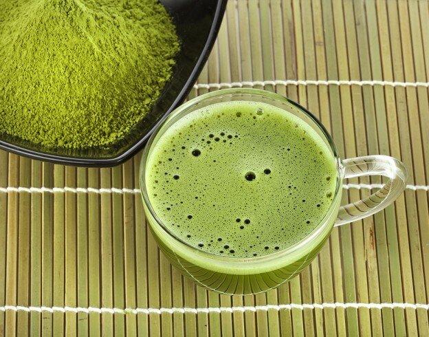 Cup of Matcha Tea on Bamboo Mat, next to bowl of Matcha Powder