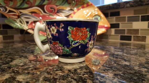 Teacup with a blue background and floral design