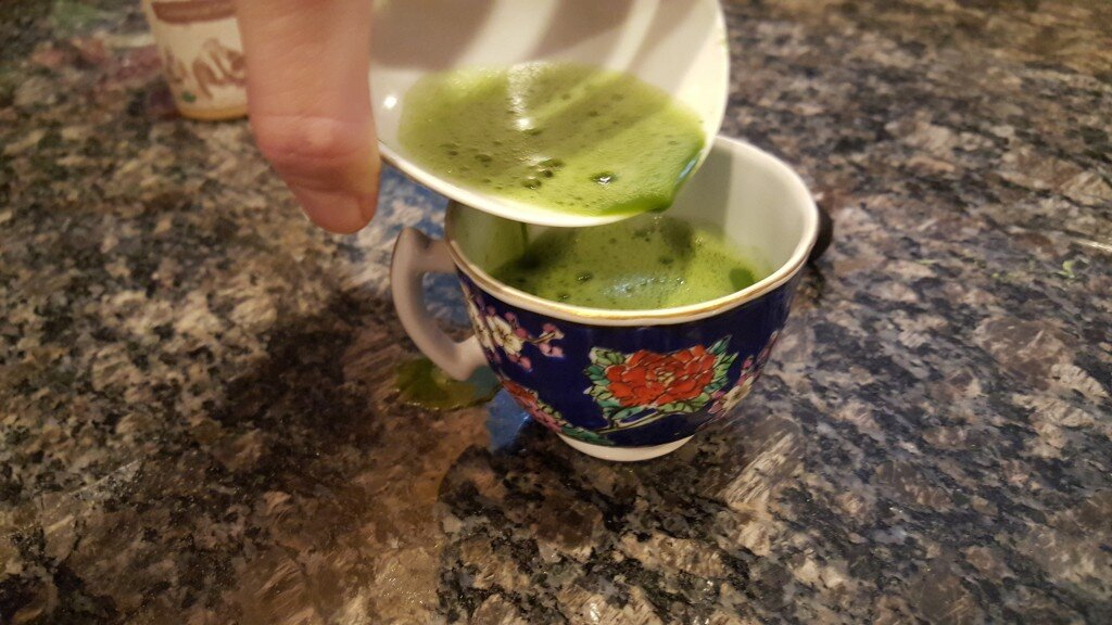 Frothy Matcha Tea being poured into blue floral teacup