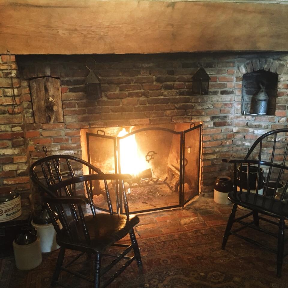 A majestic beam and brick open-hearth fireplace warms the rustic downstairs entryway. It also features plenty of visitor information to help you plan your day.
