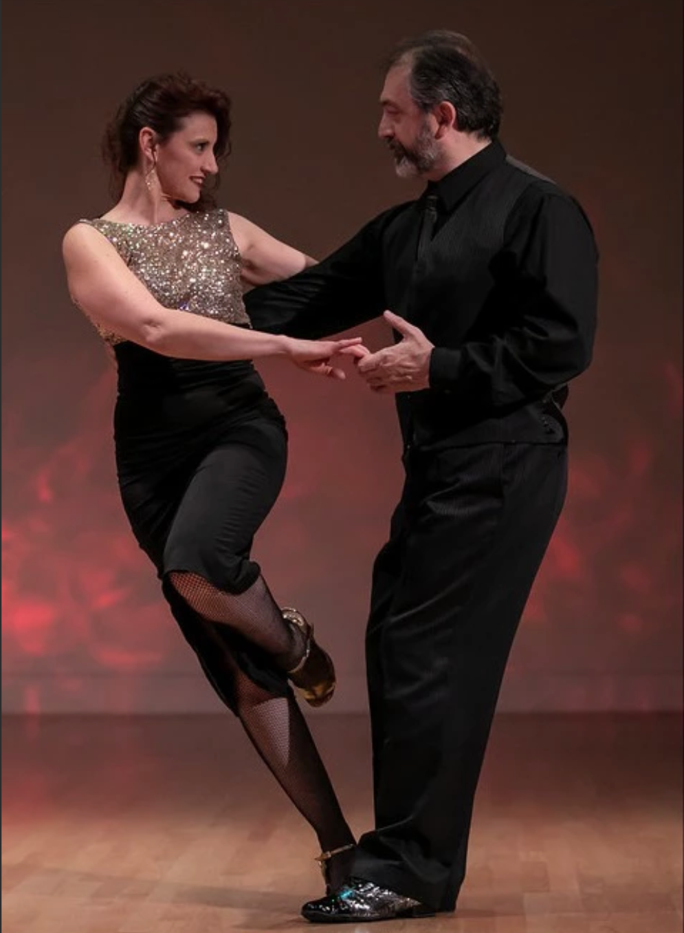 """Gustavo Naveira & Giselle Anne met in 1995 and formed a tango couple, bringing together their already-vast experience with the dance. - Together, they have successfully performed in the most important tango festivals around the world (throughout Asia, the Americas and Europe). They have also performed in the most typical milongas and theaters in Buenos Aires and abroad. Since 2003, they have been teaching in the """"tango seminar"""" format, a method which they created to enable students to genuinely progress in their dance.Gustavo Naveira deserves more credit for the resurgence and renewed popularity of tango (from the 1980s through today) than any other dancer /teacher /performer /choreographer. Since discovering the dance in the early 1980s, Gustavo has worked tirelessly to bring tango to new audiences, to evolve the dance to a higher level of technique and of structural complexity, and to develop a pedagogy that makes dancing tango at a better level possible for more people. He has also strived continuously to insure that further development of the dance be grounded in a solid historical foundation. For this reason, his dancing always has a classic look, even while he is executing the most modern and surprising steps. As early as 1999, the main Argentine newspaper Clarin stated, """"you could say that three stylistic tendencies contend for supremacy [in tango]: Urquiza's style, Almagro's style and Naveira's style.""""Giselle Anne has demonstrated her abilities as a dancer and choreographer by performing in shows such as Tango Argentino, Tango Pasión, Mariano Mores, and Los Solistas de D'Arienzo. She has performed in America, Europe and Japan. During the five years of her residence in Spain (1992-1997), she worked intensely with tango, creating her own ballet, founding a school and inaugurating the """"Casa del Tango"""" (Tango House) in Sevilla.Now with 25 years of experience, the presence and solidity of her dance are balanced perfectly with the beauty of her movements, and this"""